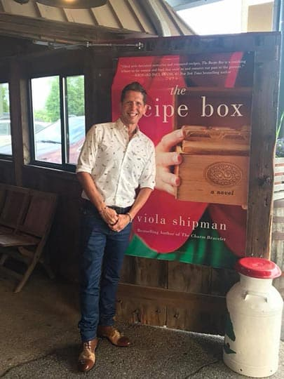 Wade Rouse/Viola Shipman in front of a poster of the cover of THE RECIPE BOX